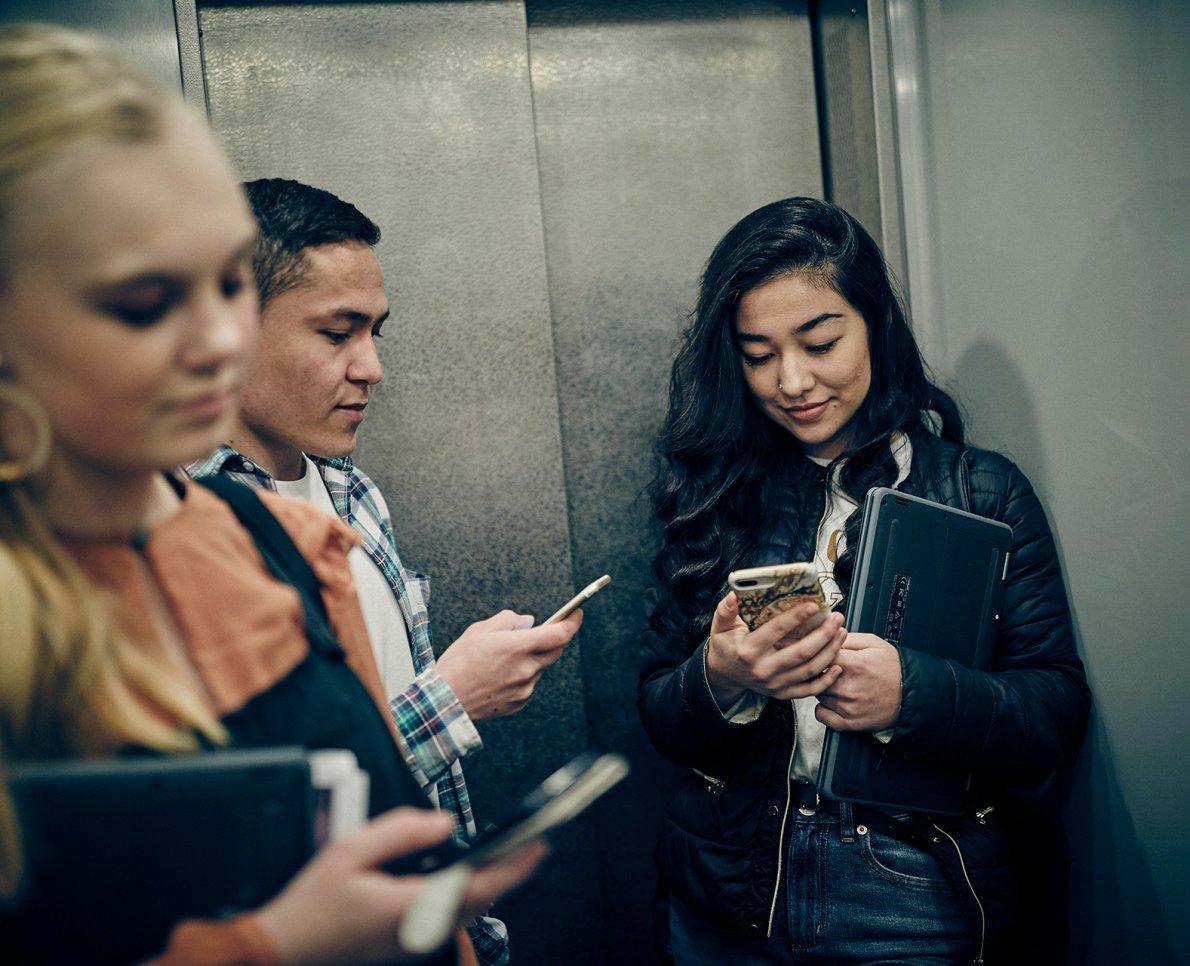 Tre elever kollar sina mobiler i hiss