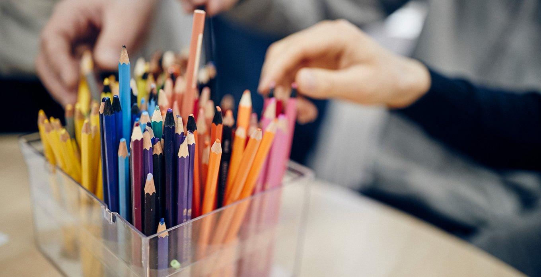 Händer som tar pennor ur pennställ