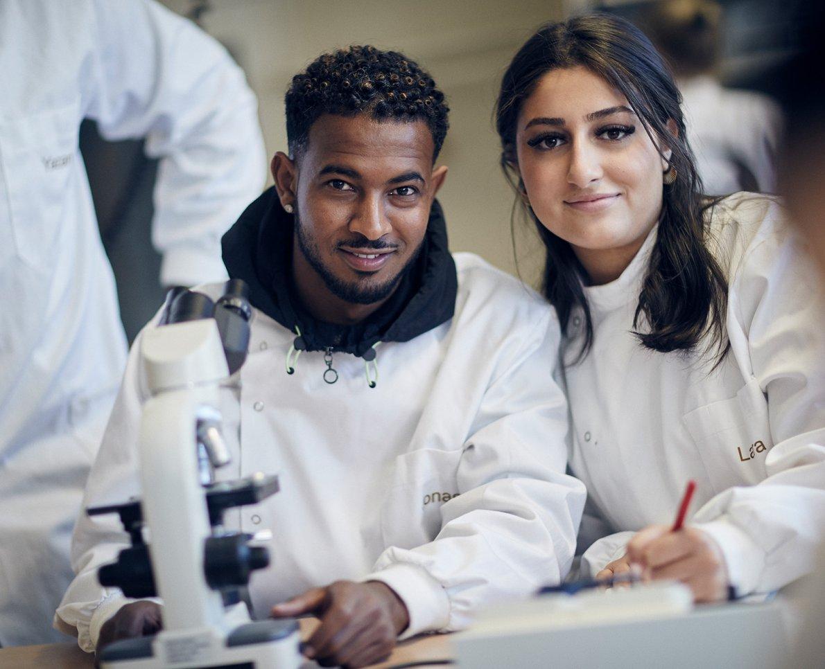 Två elever i labbrockar ler och tittar in i kameran
