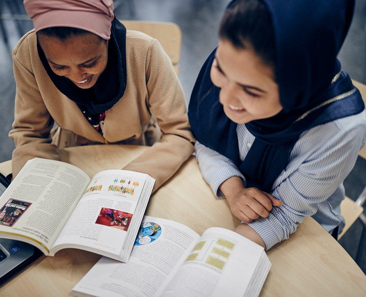 Två glada tjejer läser i böcker