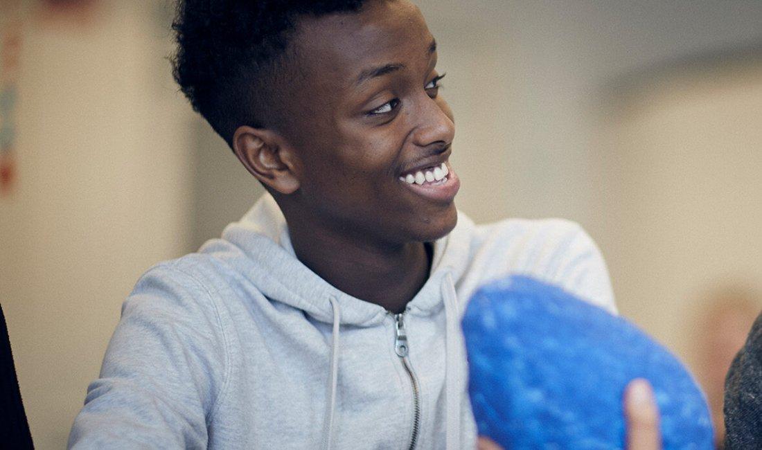 Två elever tittar på varandra och ler