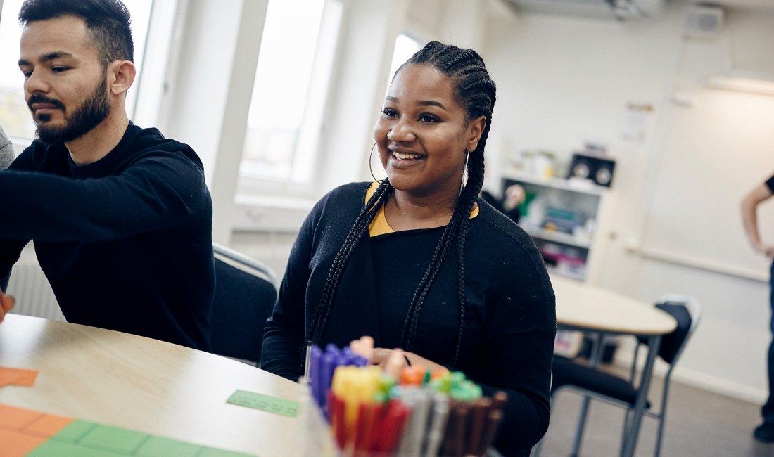 Glada elever sitter runt bord